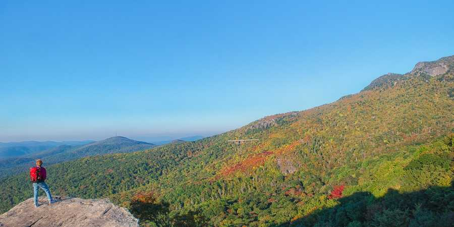 Oct. 5:A hiker gazes at the beauty from Rough Ridge, looking south toward theLinn Cove Viaduct and the peaks of Grandfather Mountain. (Photo by SkipSickler)