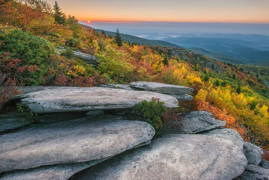 Oct. 6:The sun rises above the varied yellows, oranges and greens of Rough Ridge,off the Blue Ridge Parkway. (Photo by Skip Sickler) Brisk winds this weekend shook off just enough leaves in the High Countryto create a satisfying crunch beneath hikers' feet, but not enough todiminish the colorful hues at the higher elevations.