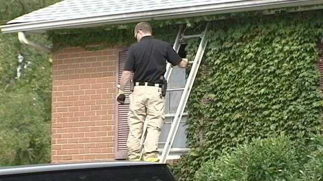 Crews at the scene Tuesday knocked out some of the windows of the home. Deputies wearing yellow exposure coveralls later entered the residence.