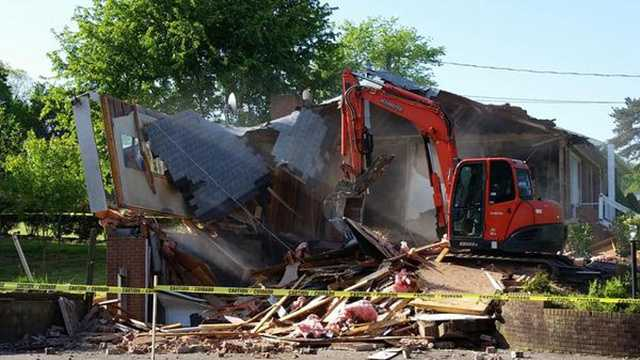 Demolition began Friday at a Clemmons home where the skeletal remains of two people were found in October.
