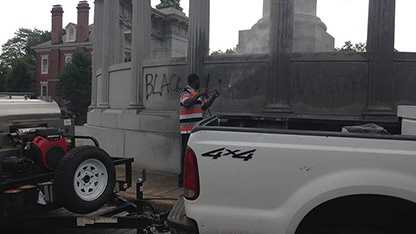 Crews clean up vandalism at a monument to former Confederate president Jefferson Davis in Richmond.