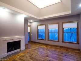 This room has a fireplace, hardwood floors and a trey ceiling