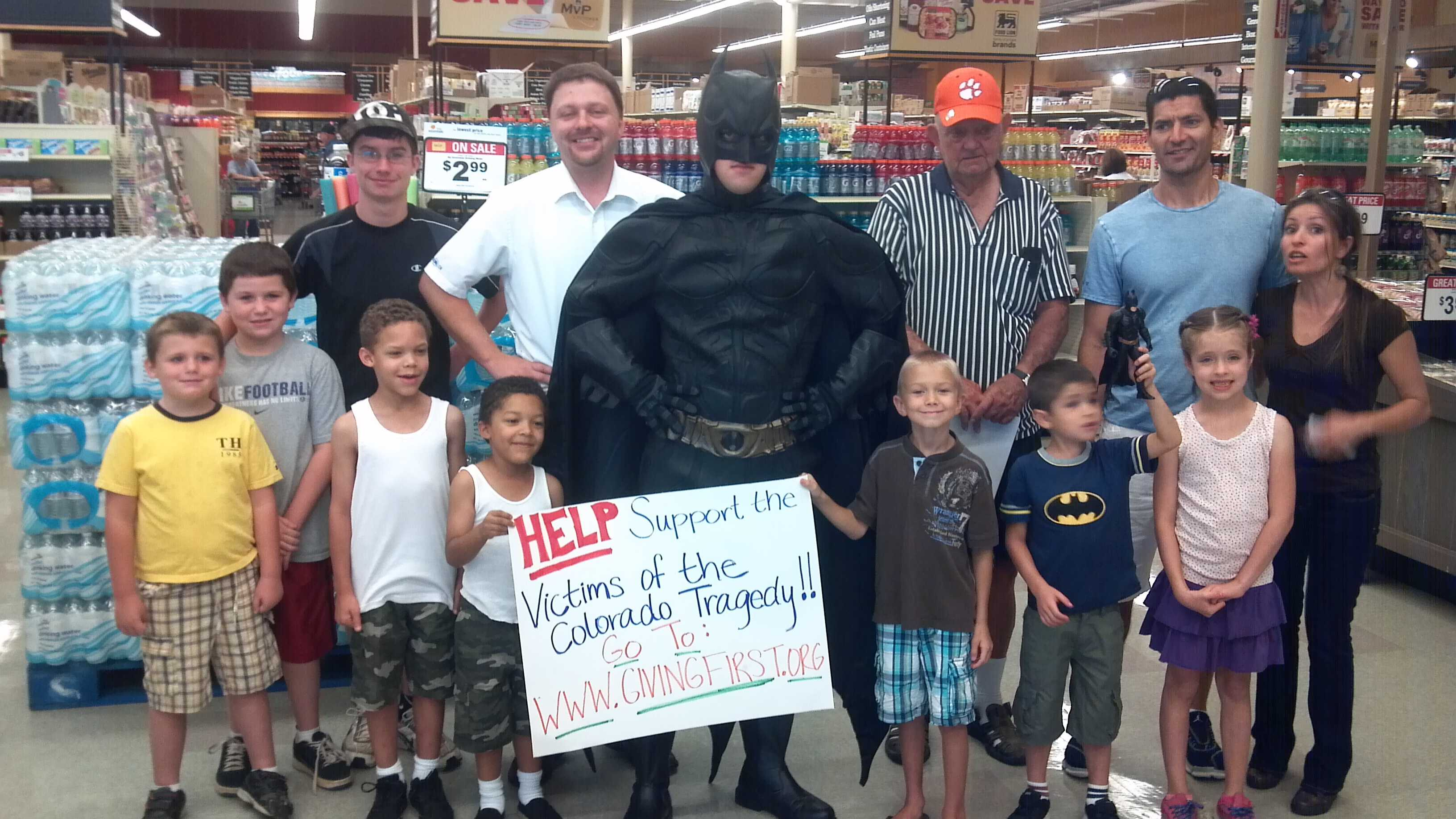 Batman joins store manager, Jeremy Fuller (in white), and fans at the Food Lion in Greenwood for a fundraiser to benefit the Colorado theater shooting victims.