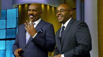 """Steve Harvey: (1957- ) Broderick Steven """"Steve"""" Harvey is an American entertainer and author who hosts The Steve Harvey Morning Show and Family Feud. (Shown with Nigel Robertson)"""