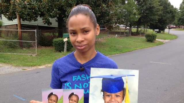 Janay Edwards holds pictures of daughter, Sariyyah, 5, a K5 student at Duncan Elementary