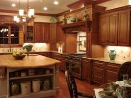 The gourmet kitchen has custom distressed-cherry cabinetry, high-end appliances, granite counters and a large maple butcher block island.