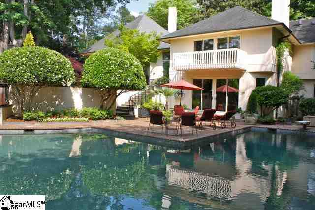 A classic in-ground pool and lounge area adjoin patio areas, walking trails and meticulous landscaping.