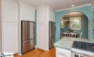 The kitchen features two stainless steel refrigerators, a six burner gas stove, an ice maker, beverage center, and stainless steel oven, and warmer drawer, new two drawer style dishwasher with custom cabinet front.