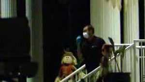 A masked worker comes out of Overbrook Child Development Center Tuesday night.