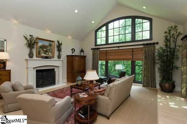 The living room/library/great room has cathedral ceiling and palladium windows overlooking a private wooded lot.