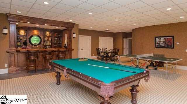 The lower level features media/game room with a wine bar and kitchen area.
