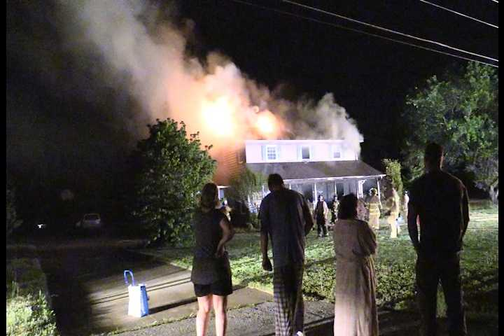 A small crowd gathers to watch as firefighters battle the flames at a home on Concord Road in Anderson County.
