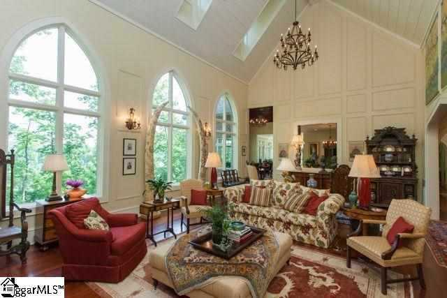 The great room has a limestone fireplace, vaulted ceiling, built-in book shelves, large arched custom windows which bring the view inside and molding detail on the walls.