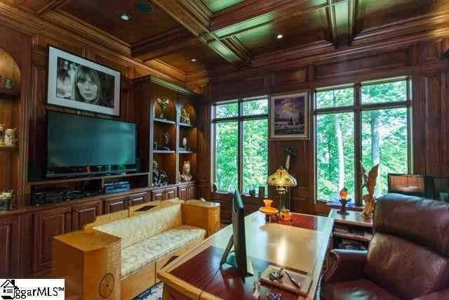 The other is paneled in hardwoods from the coffered ceiling to the paneled walls and built in bookshelves.