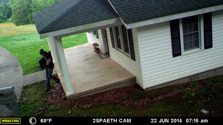 You can see the man wearing a bandana in this photo as he carries a television from the home.