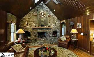 The great room is large with cherry stained cypress walls, cathedral ceiling and a massive stone fireplace.