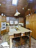 The kitchen has a large center island with room for at least six family members or guests.