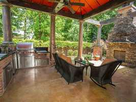 The sunroom leads to a full outdoor kitchen. The outdoor area is encircled by a brick fence. This home is featured on realtor.com for $1,800,000.