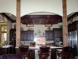 The home has 3 kitchens. The main kitchen has a butler's pantry and multiple ovens including Wolf Gas Range.
