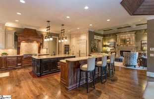 The kitchen features two dishwashers, a center island with vegetable sink, breakfast bar, double convection ovens, warming drawer, wine cooler, Wolf 6 burner gas cook top and a built in sub zero refrigerator.