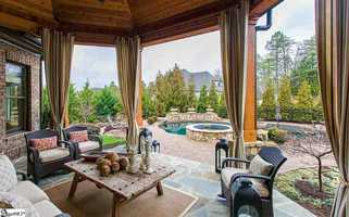 The windows look to a covered porch and pool. The home also has a summer kitchen with grill, outdoor fireplace and fenced backyard.