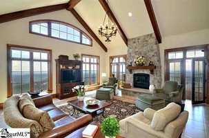 Features include copper roofing accents, custom arched mahogany double entry doors with antique german glass panes and Tennessee crab orchard patios.