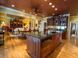 There is a open foyer that leads to the living space which includes a gourmet kitchen, wet bar, den and library.