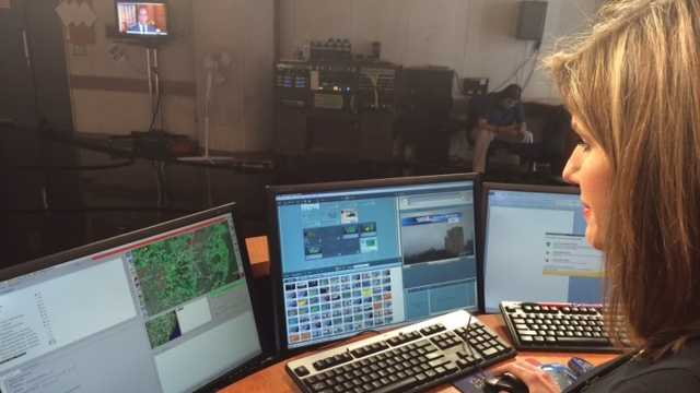 Meteorologist Pamela Wright views the green on the screen that indicates rainy weather.