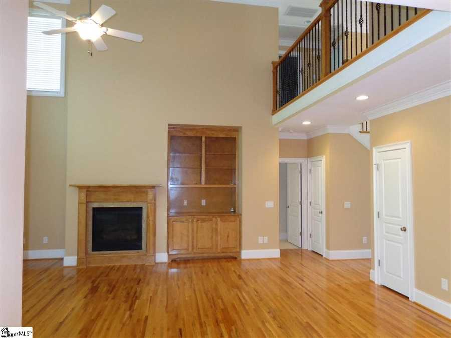The 2-story home has an open floor plan, crown molding throughout and wrought iron spindles on the lit stairwell. The great room has a vaulted ceiling with remote control blinds, built in bookshelves and a fireplace with gas logs.