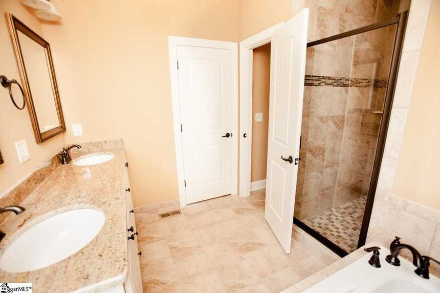 The master suite as 2 walk in closets, a separate tile shower, dual sinks and a large tub.