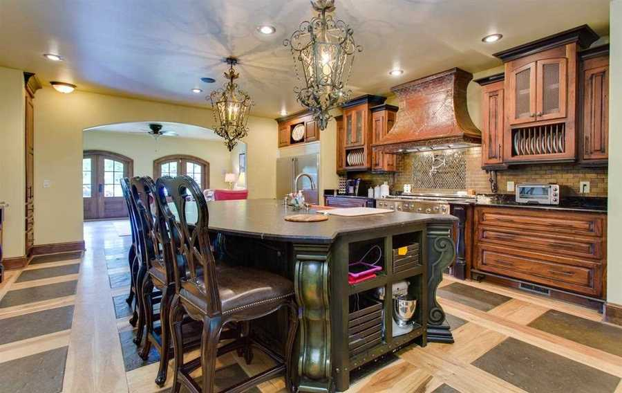 The center island in the kitchen is leatherized granite and the kitchen also a copper farmers sink.