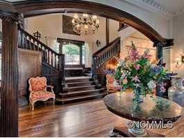 The formal entry is graced by 20' ceilings and an original chandelier that is suspended over the grand staircase and surrounding balcony.