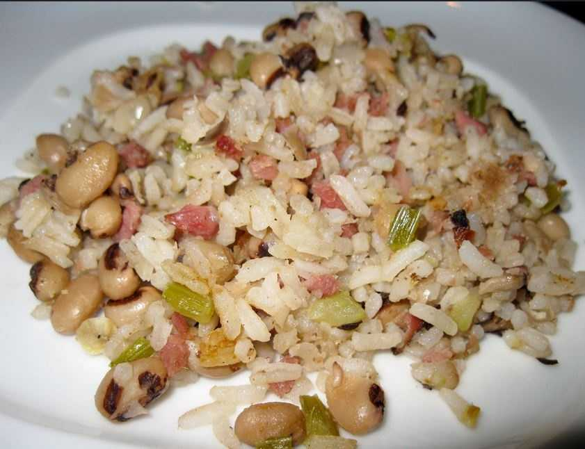 """The origin of the Hoppin' John name is unclear. One legend credits a crippled old man named John who sold peas and rice in the streets of Charleston. Some food historians say it was derived phonetically from the French term for dried peas, """"pois pigeons."""""""