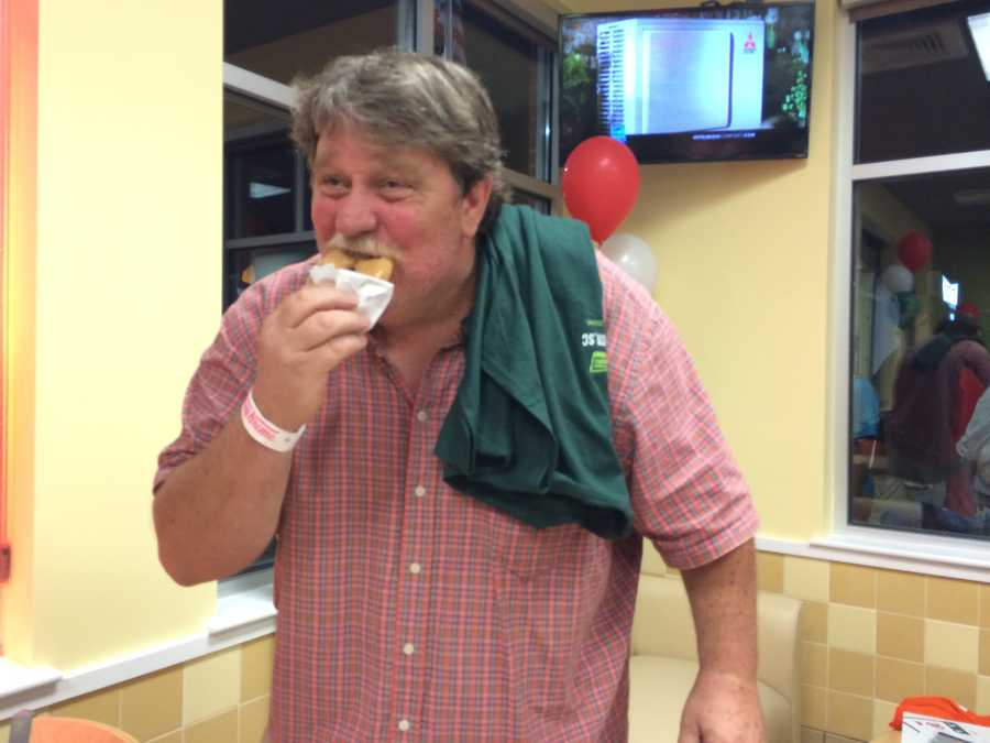 Tony Hawkins was the fourth person in line, and enjoys his first donut of the day.