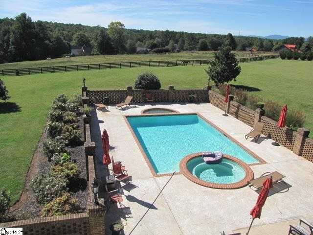 The home features an in-ground pool with a hot tub
