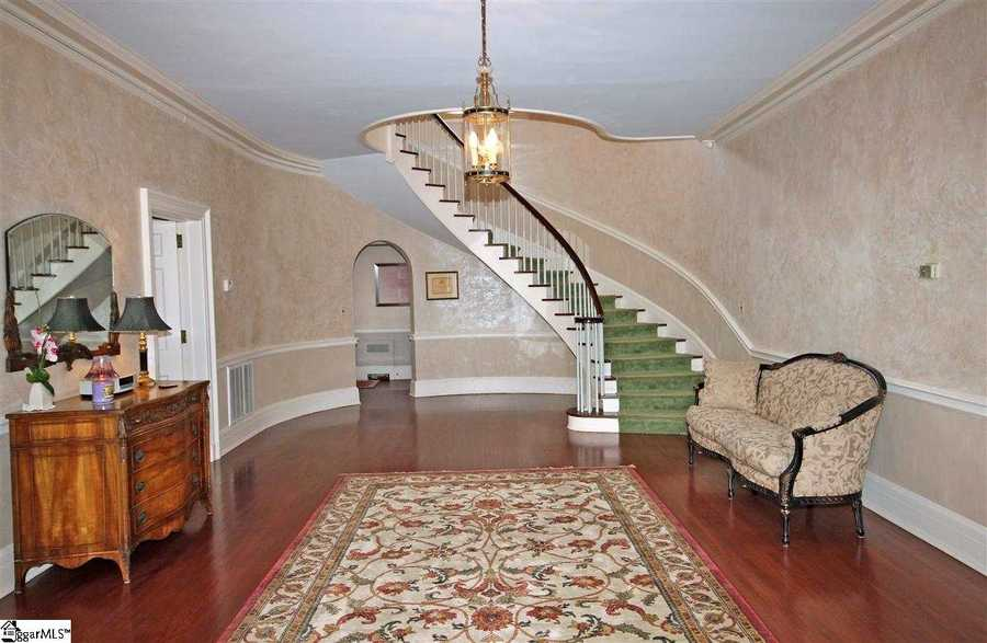 The restored Neo Classic mansion features a semi-circular staircase that is the focus of a large foyer.