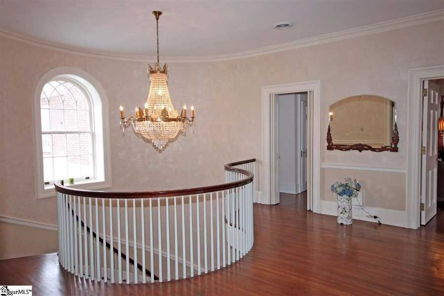 The home has hardwood floors with inlaid borders, oversized windows, a fireplace, wide moldings, crystal chandeliers, and dual doors that open to side porches.