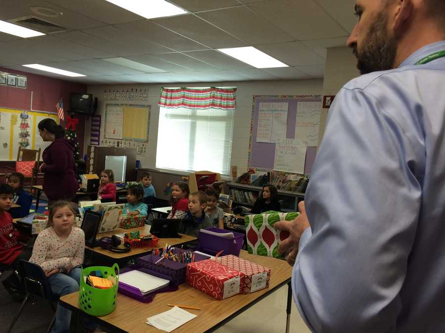Principal Tom Miller passes out the presents to a first grade class at Berea Elementary School.
