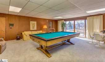 In a separate wing there are four bedrooms and a large recreation room on the lower level.