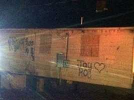 Graffiti on the side of the boarded-up home appears to be messages to the man found shot dead there last week.
