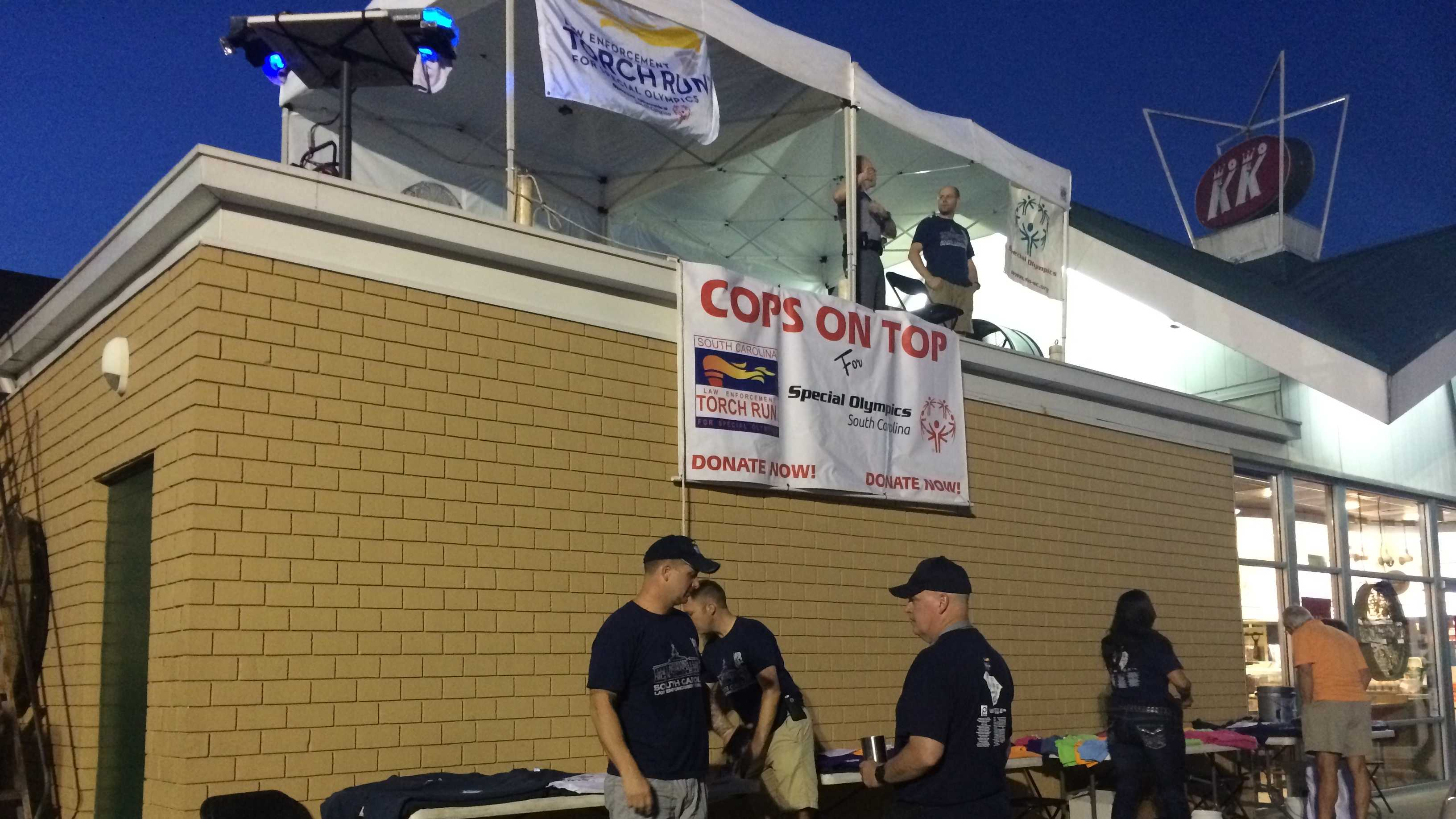 Officers and deputies with local law enforcement agencies begin their Cops on Top of a Doughnut Shop fundraiser.