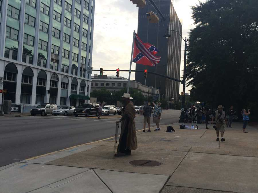 A confederate flag supporter flies the flag in front of the Statehouse on the morning after the historic vote.