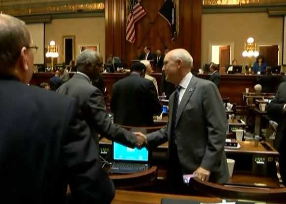 Lawmakers, after adjourning, shake hands.