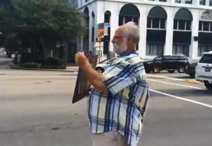 """A Confederate flag protester holds a sign in front of the Statehouse reading, """"We won,"""" as passing cars honk."""