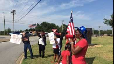 A group gathers along a busy Greenville intersection to ask drivers to honk against racism.