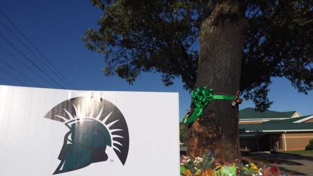 A color memorial marks the site where a crash killed four USC Upstate students and injured a fifth.