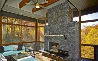 Two massive stone fireplaces, each three stories tall on inside and outside, bisect the home.