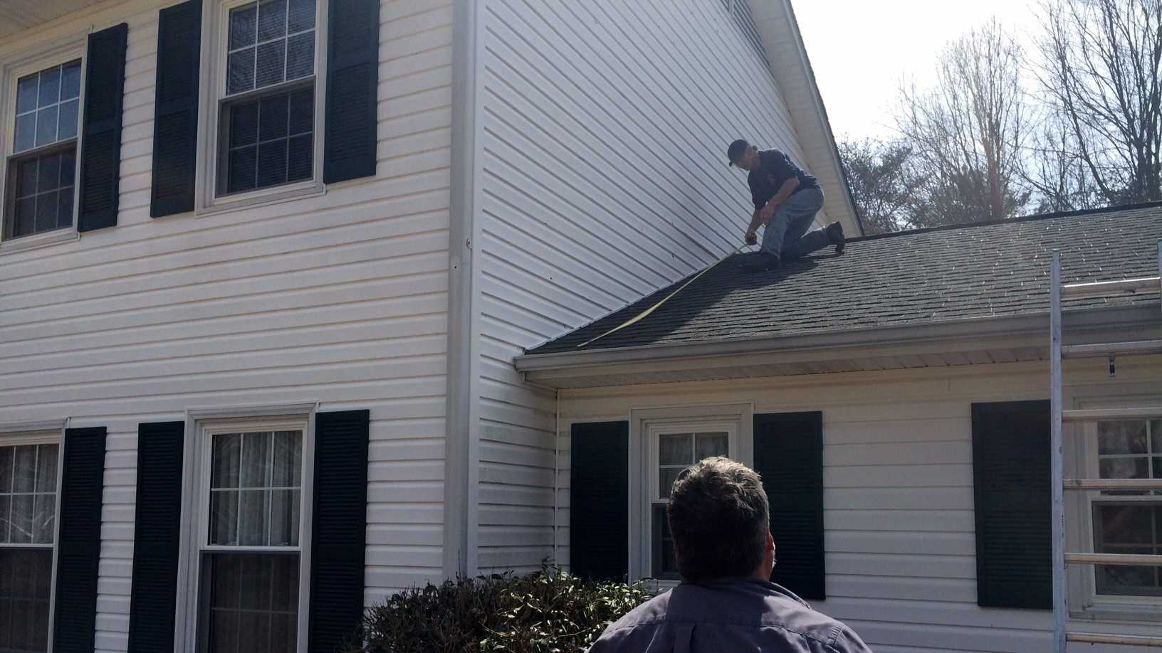 A crew from Roebuck Roofing and Construction surveys the hail damage on a home in Spartanburg County.