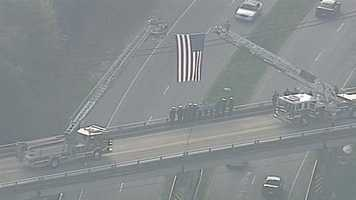 Officers make their way to the funeral. An American Flag hangs from a ladder truck on the overpass.