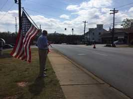 A man waits for the funeral procession with a flag